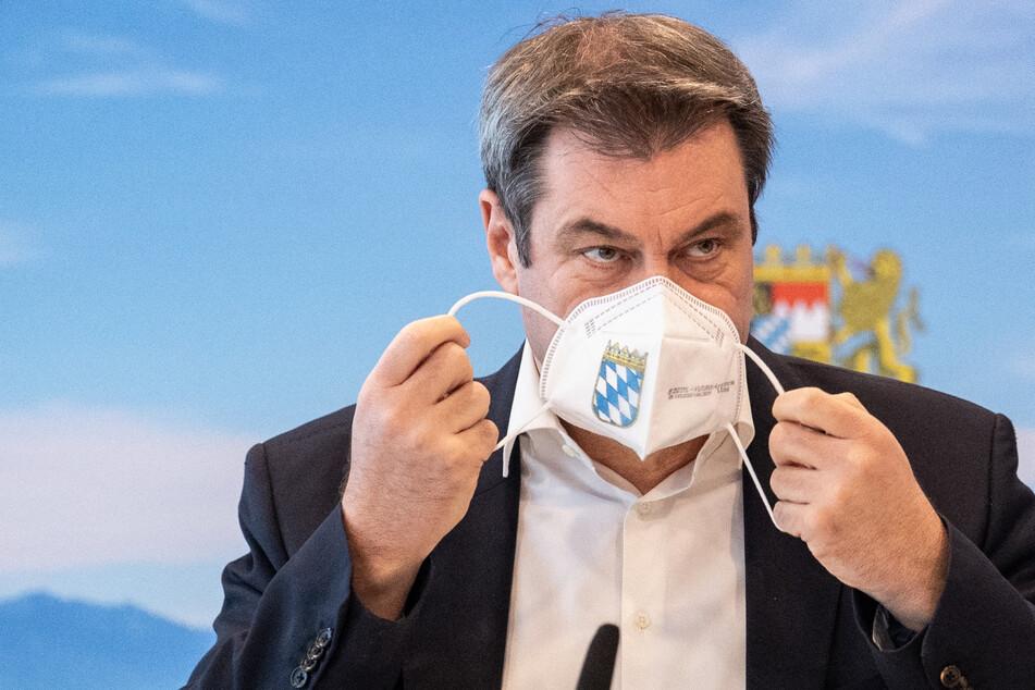 Markus Söder (CSU), Parteivorsitzender und Ministerpräsident von Bayern, nimmt zu Beginn einer Konferenz seine FFP2-Maske ab.