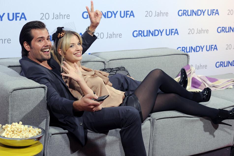 Daniel Fehlow und Susan Sideropoulos auf einer Couch posierend vor den Kameras.