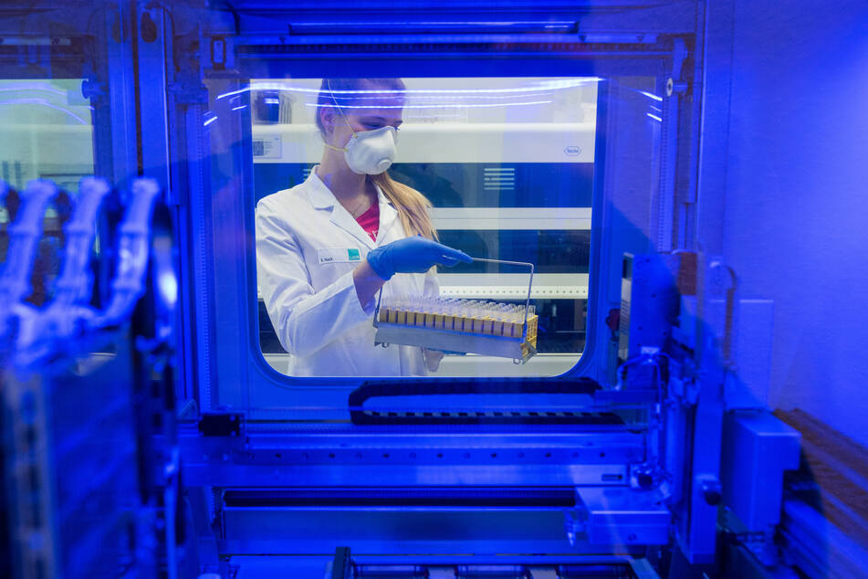 Katrin Haack, Biologielaborantin des Laborverbundes Dr. Kramer und Kollegen, hält Proben auf das SARS-CoV-2-Virus und steht dabei hinter einem Großgerät zur Analyse.
