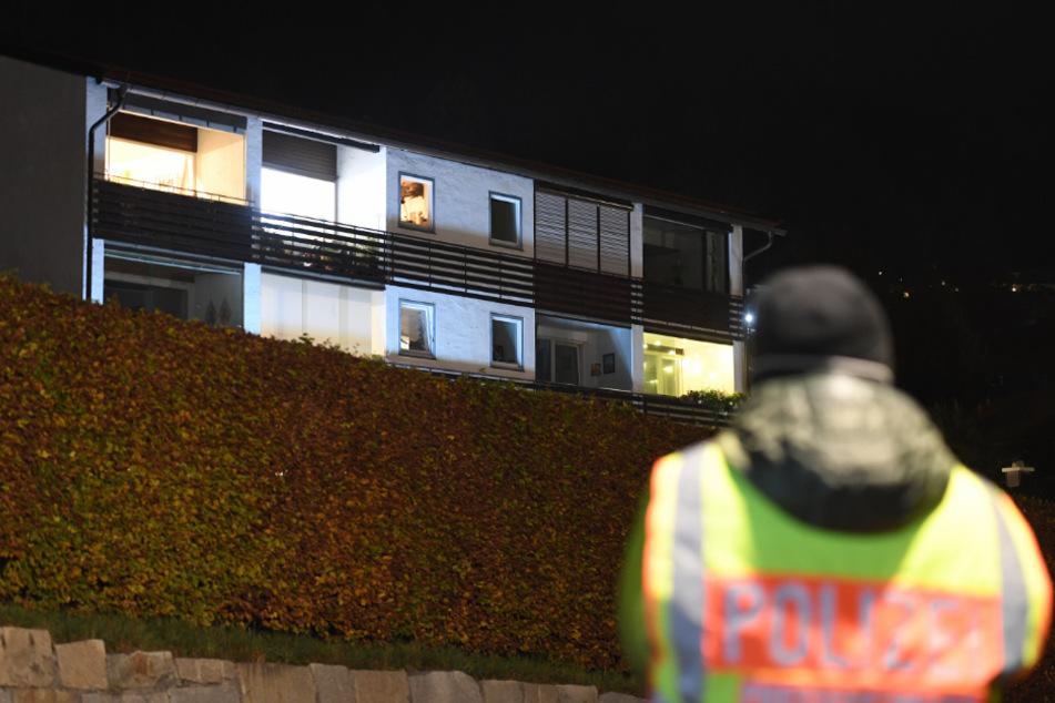 Ein Polizist steht vor dem Mehrfamilienhaus in Tegernsee in dem sich die schreckliche Tat abspielte.