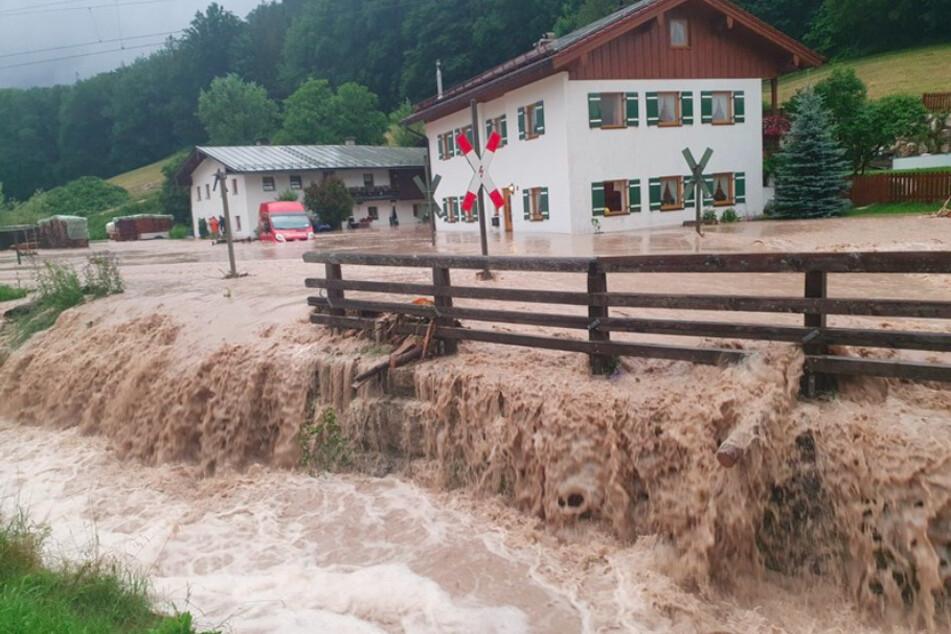 Wasser fließt über einen Platz vor einem Haus. Der Landkreis Berchtesgadener Land hat nach starkem Regen wegen Hochwassers den Katastrophenfall ausgerufen.