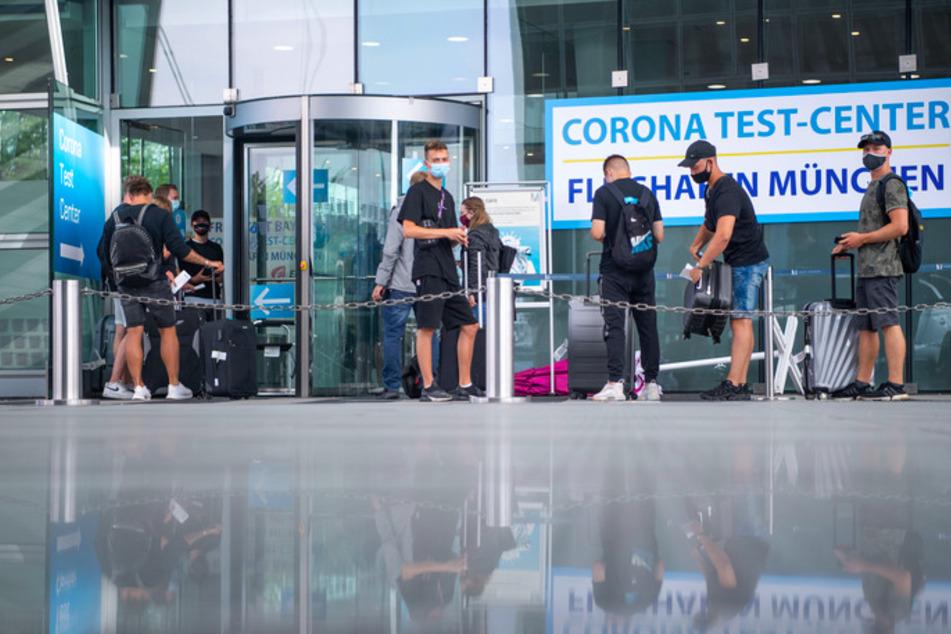 Eine Reisegruppe steht vor dem Corona Test Center am Münchener Flughafen.