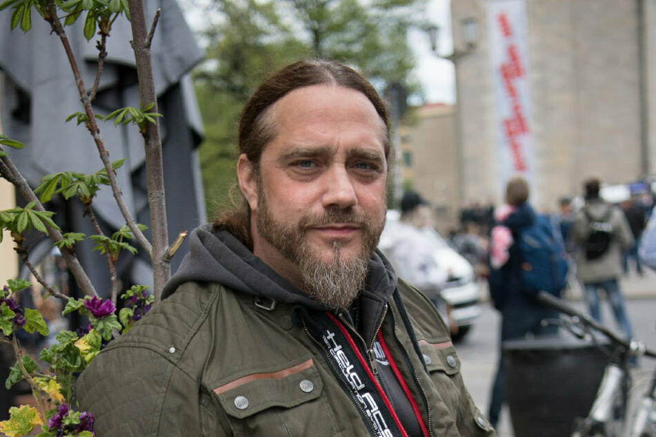Der Musiker Martin Kesici beobachtet als Anwohner eine Kundgebung gegen die Corona-Einschränkungen.