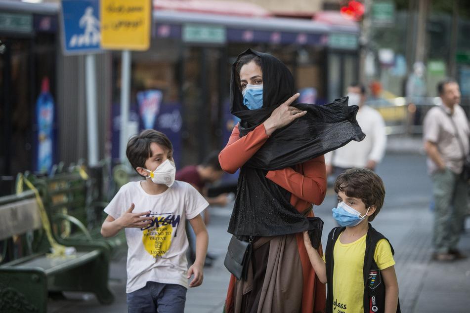 """Kinder mit Gesichtsmasken gehen mit ihrer Mutter eine Straße in Teheran entlang. Die Corona-Situation im Iran sieht laut dem dortigen Vizegesundheitsminister """"gar nicht gut"""" aus. (Archivbild)"""