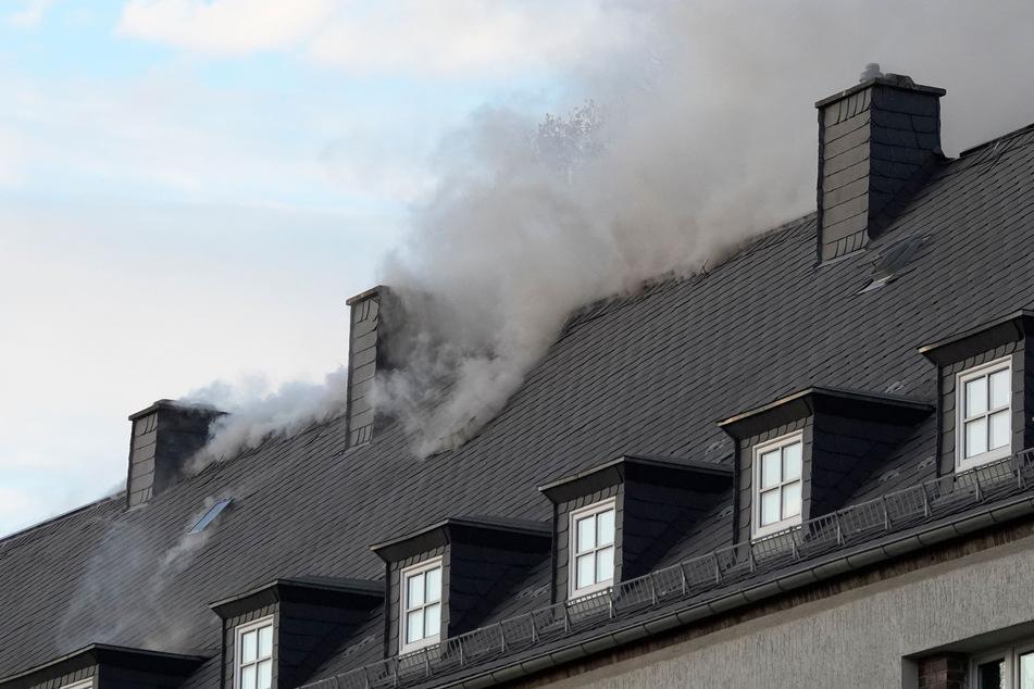 Aus dem Dach des Mehrfamilienhauses stiegen dunkle Rauchwolken auf.
