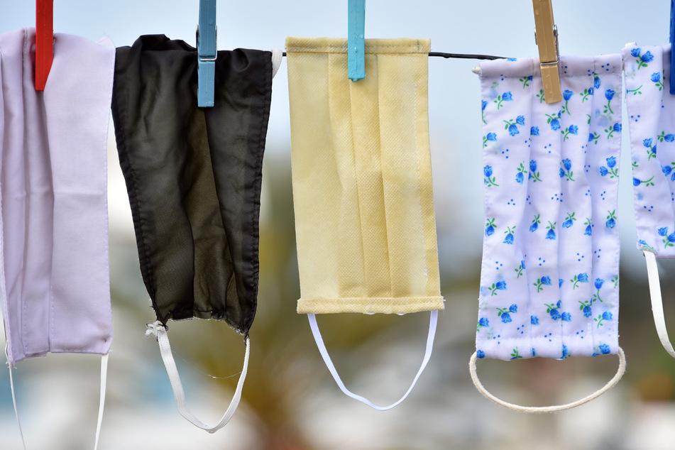 Mundschutze hängen zum Trocknen über einer Leine. (Symbolbild)