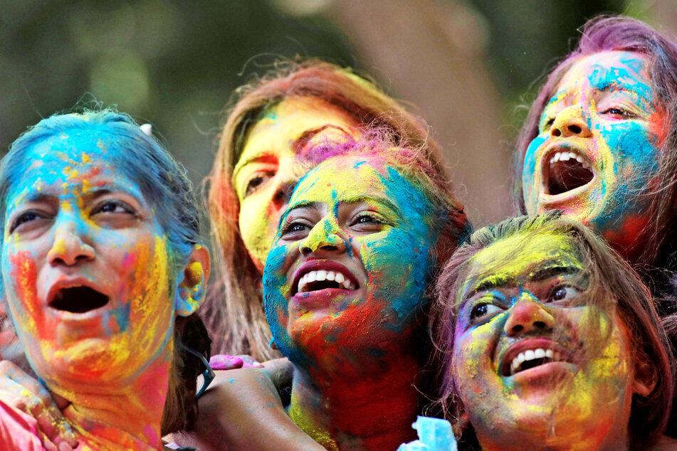 Frauen, deren Gesichter mit farbigem Puder beschmiert sind, jubeln während der Feierlichkeiten zum Holi-Fest in Mumbai, Indien.