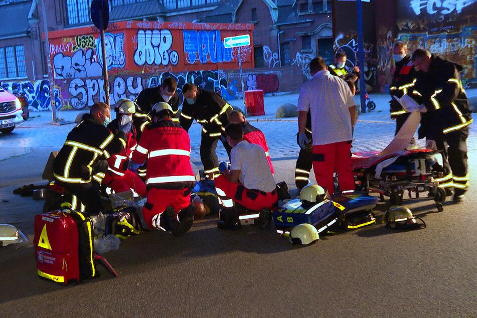 Rettungskräfte versorgen den schwer verletzten Mann, nachdem er im Schlaf von dem Lkw überrollt wurde.