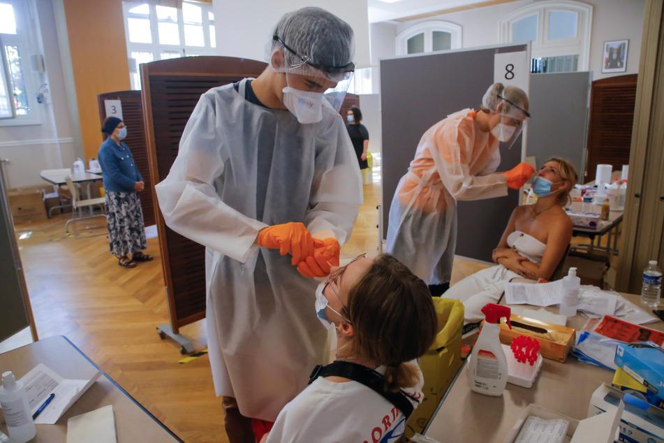 Mitarbeitern des Gesundheitswesens nehmen bei zwei Frauen Nasenabstriche für einen Covid-19-Test. Angesichts der steigenden Zahlen von Virusfällen hat Frankreich Mühe, genügend Tests durchzuführen, um den Anforderungen gerecht zu werden.