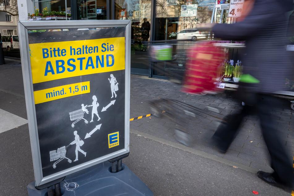 Schilder vor den Supermärkten warnen vor der Ansteckungsgefahr.