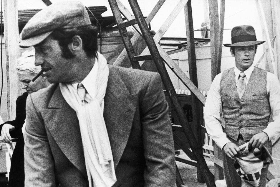 """Belmondo (l.) und sein Schauspiel-Kollege Alain Delon im Januar 1969 in Marseille bei den Dreharbeiten zum Film """"Borsalino"""". (Archivbild)"""