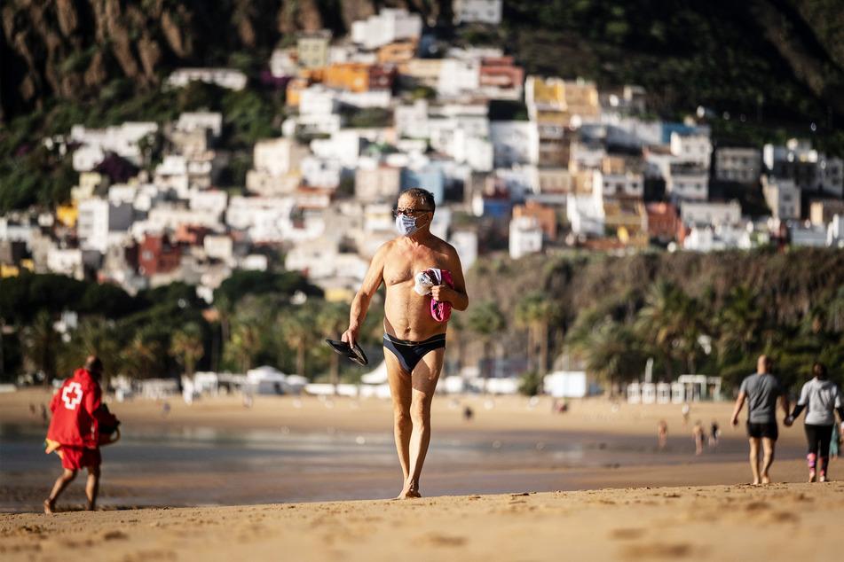 Ein Mann mit Maske spaziert an einem wenig besuchten Strand auf Teneriffa.