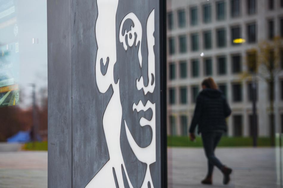 Eine Frau spiegelt sich in einer Gebäude-Fassade mit dem Portaits des Dichters auf dem Campus Westend der Goethe-Universität.