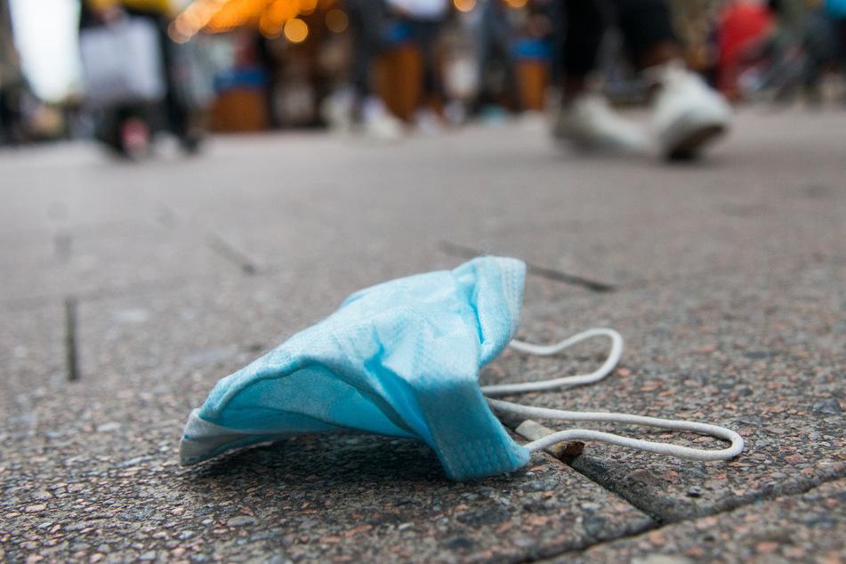 Eine Maske liegt in der Innenstadt auf dem Boden.