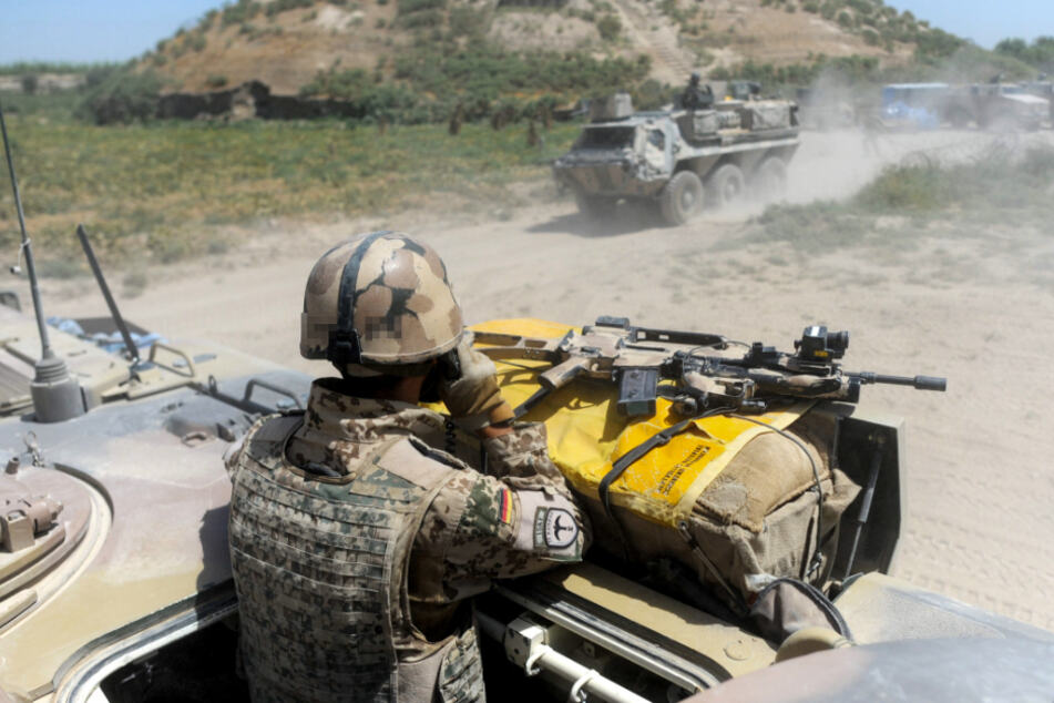 Afghanistan, Kundus: Bundeswehrsoldaten fahren 2011 während eines Einsatzes durch das Gelände.