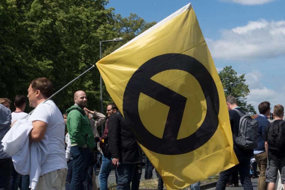 """Ein Anhänger der rechtsradikalen """"Identitären Bewegung"""" geht am 17.06.2017 in Berlin mit einer Fahne auf der Brunnenstraße. (Archivbild)"""