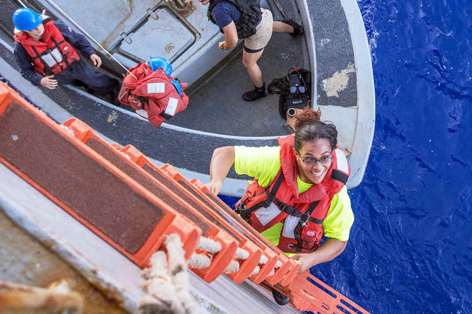 Matrosen der USS Ashland begrüßen nach der Rettung Hund Zeus und seine Besitzerin Tasha Fuiaba an Bord.