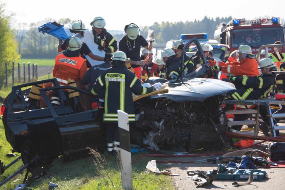 Einsatzkräfte befreien den Fahrer aus dem Unfallwagen.