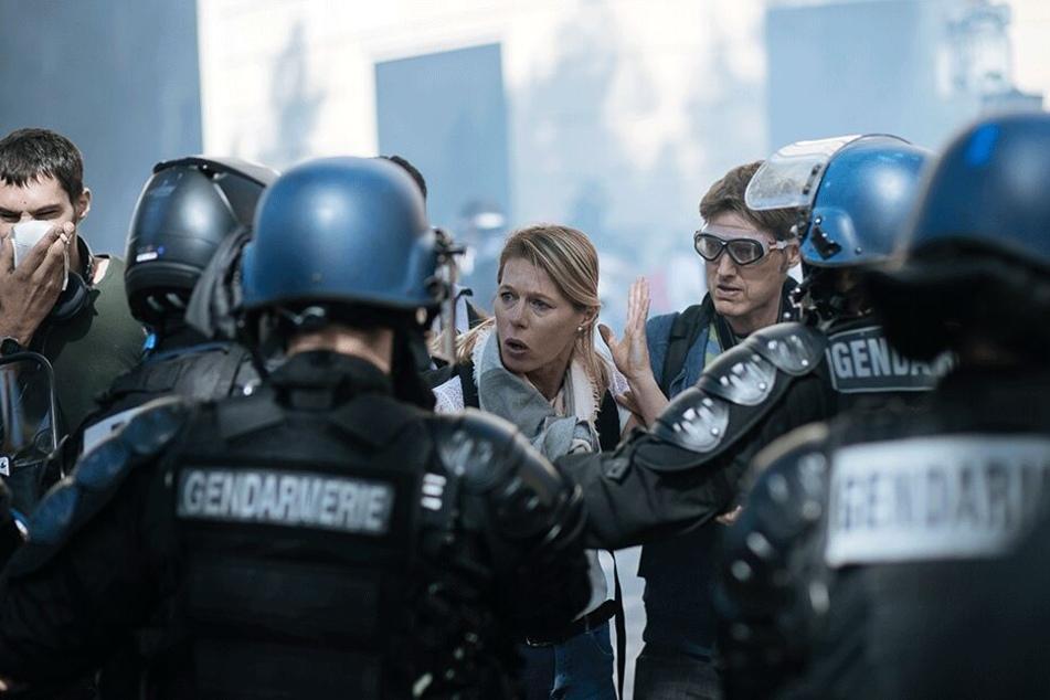 """Eine Frau gestikuliert bei einer """"Gelbwesten""""-Demonstration während sie mit Polizisten spricht."""