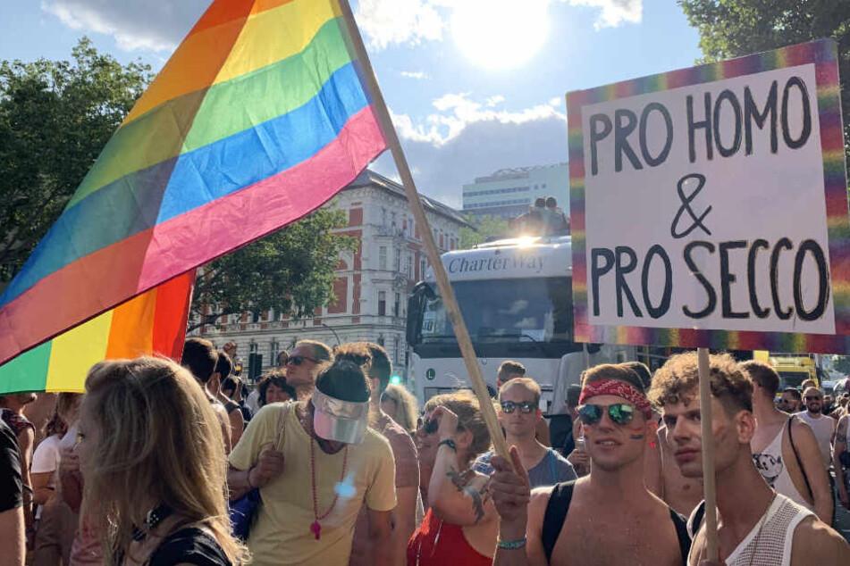 """Teilnehmer der CSD-Parade am 27.07.2019 in Berlin alten ein Plakat mit der Aufschrift """"Pro Homo & Pro Secco"""" und eine Regenbogenfahne."""