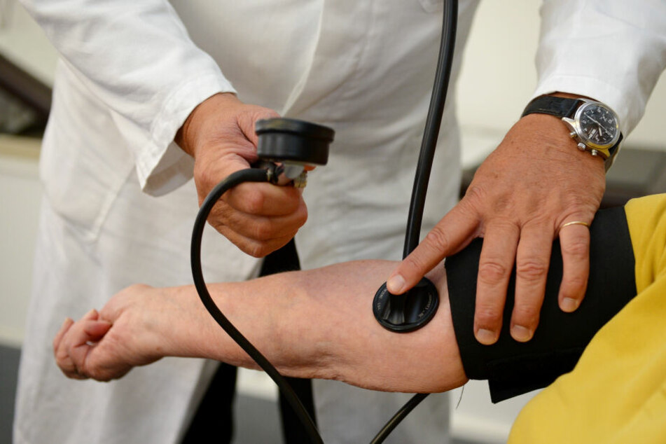 Ein Arzt misst bei einer Patientin den Blutdruck.
