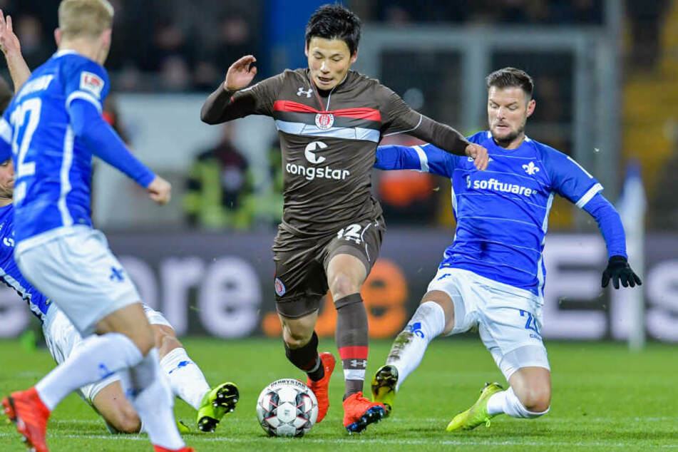 St. Paulis Ryo Miyaichi (links) und Darmstadts Marcel Heller im Zweikampf um den Ball.
