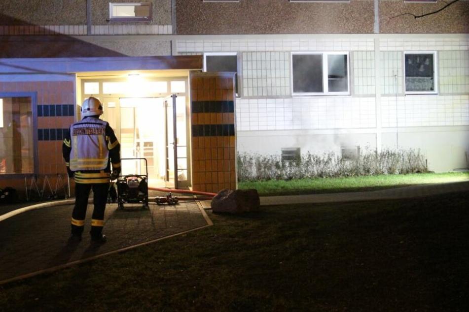 Ein Feuerwehrkamerad steht vor dem Hauseingang eines Plattenbaus in der Ludwigsburger Straße. Rechts neben ihm steigt Rauch aus dem Keller auf.