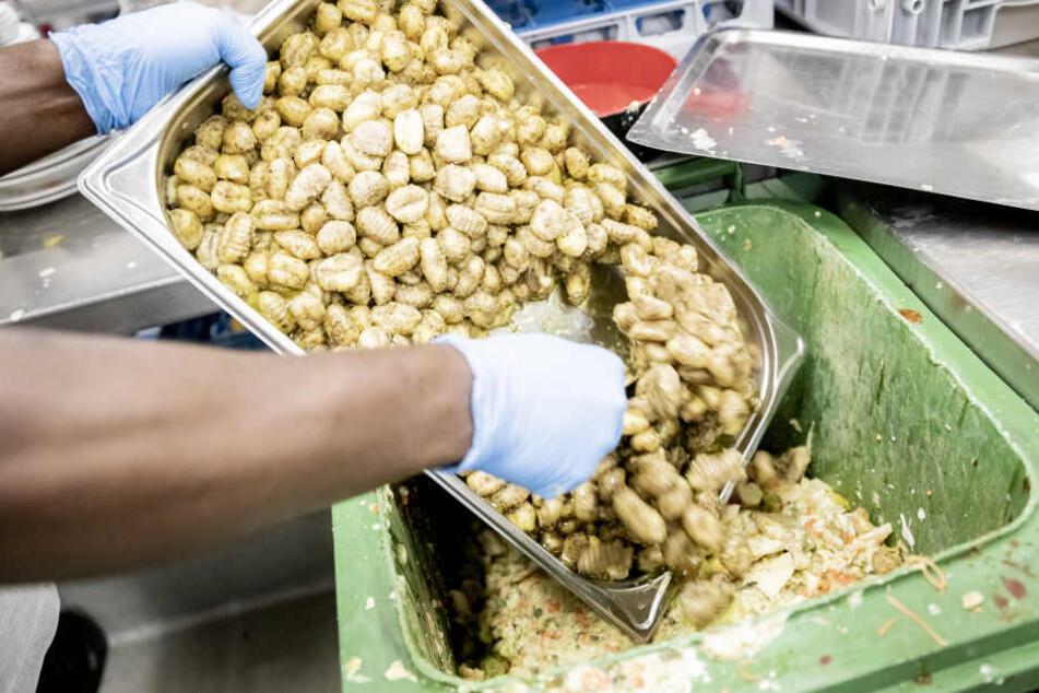 Ein Mitarbeiter des H4 Hotels in Berlin leert in der Küche Lebensmittelabfälle in eine Tonne. Hier werden verschiedenen Lebensmittelabfälle analysiert um diese zukünftig besser zu vermeiden.