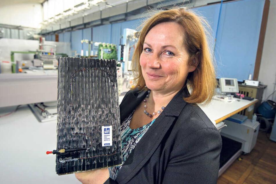Elke Thiele vom STFI zeigt ein Betonteil mit der Überwachungs-Glasfaser, die  in einer Steckverbindung für Messgeräte endet.