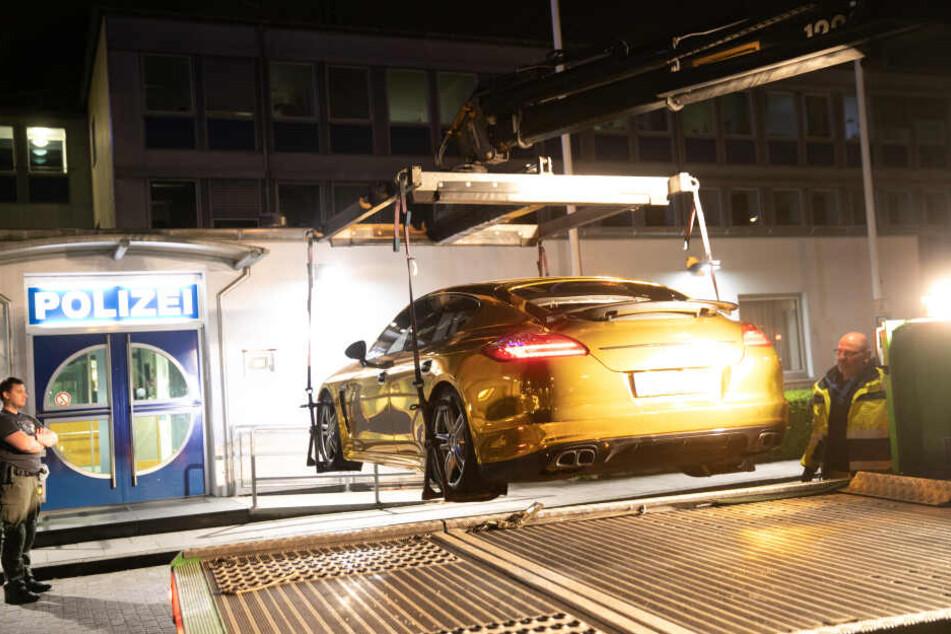 Ein Polizist steht vor einer Polizeiwache an einem mit Goldfolie beklebten Porsche Panamera, der auf einen Fahrzeugtransporter verladen wird.