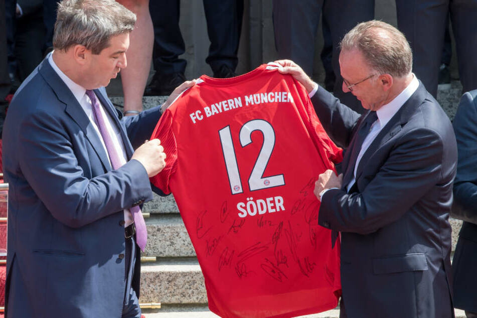 Karl-Heinz Rummenigge (2.v.l.), Vorsitzender des FC Bayern München, überreicht während eines Empfangs in der bayerischen Staatskanzlei Markus Söder (CSU), Ministerpräsident von Bayern, ein Fußball-Trikot mit der Nummer 12.