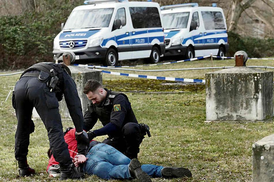 Zwei Bereitschaftspolizisten haben nach einem simulierten Straßenraub unter Jugendlichen einen Verdächtigen am Boden fixiert.