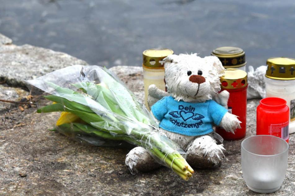 Blumen, Kerzen und ein Plüschtier liegen an einem Weiher in der Nähe des Fundortes einer Babyleiche. (Archivbild)