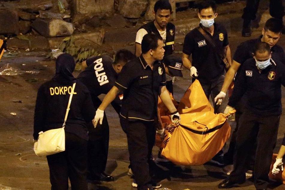 Polizisten tragen in Jakarta (Indonesien) einen Leichensack von einem Tatort weg (Archivbild).