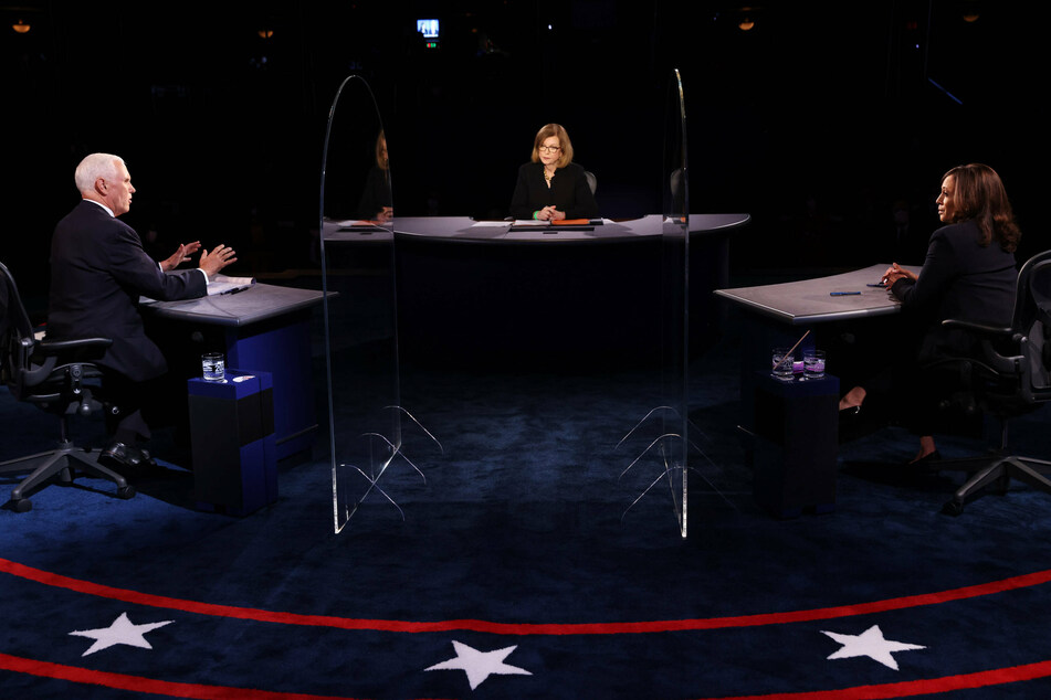 Vice President Mike Pence (l.) and Kamala Harris debate each other from behind two plexiglass screens.