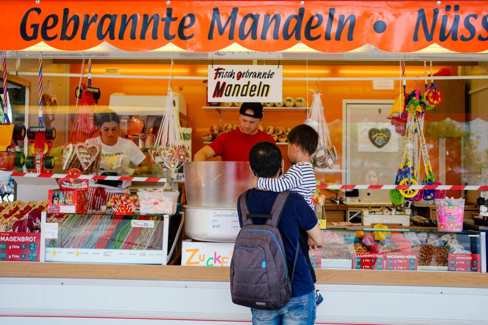 Kunden warten vor einem Schaustellerwagen, der Zuckerwatte und gebrannte Mandeln anbietet, auf eine Portion Zuckerwatte.