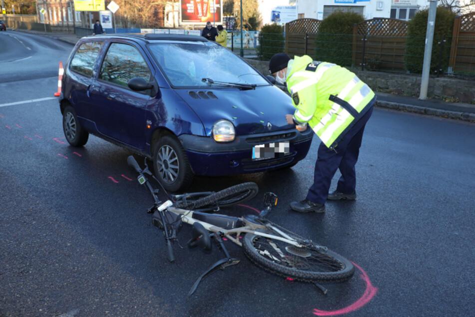 Ein Polizist inspiziert die Schäden am Renault.