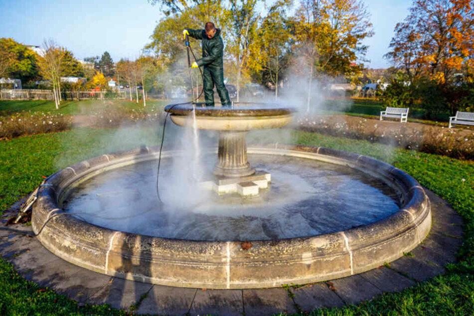 Klaus Schönberg (54) kärchert den Brunnen im Blüherpark mit Hochdruck und  Wasserdampf.