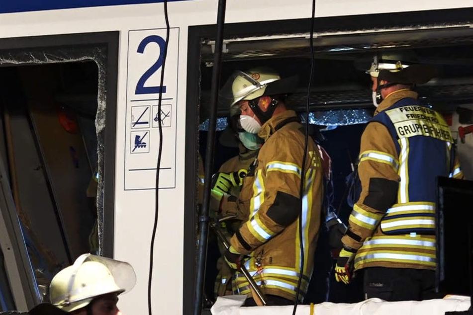 Rettungskräfte stehen in dem Wrack des Personenzuges.