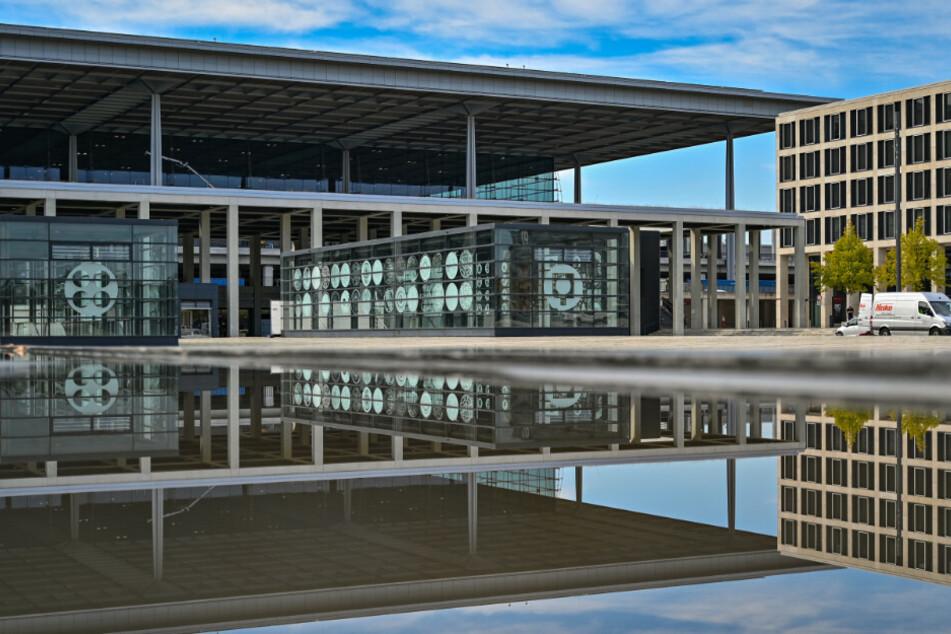 """Das Hauptterminal vom Flughafen Berlin Brandenburg """"Willy Brandt"""" (BER) spiegelt sich im Wasser eines Springbrunnens."""