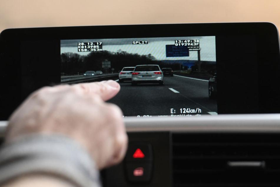 Ein Beamter der Verkehrspolizei in Freiburg schaut sich auf dem Monitor des Videomessfahrzeuges einen Autofahrer an, der beim Drängeln auf der Autobahn gefilmt wurde. (Archivbild)