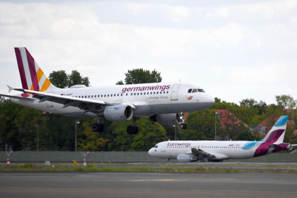 Ein Flugzeug der Airline Germanwings landet auf dem Flughafen Tegel, während im Hintergrund ein Flugzeug der Airline Eurowings auf dem Rollfeld steht. (Archivbild)