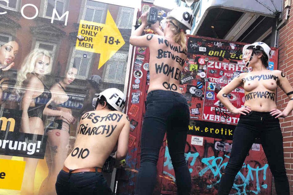 Die Aktivistinnen demontieren mit nackten Oberkörpern und einer Flex den Sichtschutz der Herbertstraße in Hamburg.