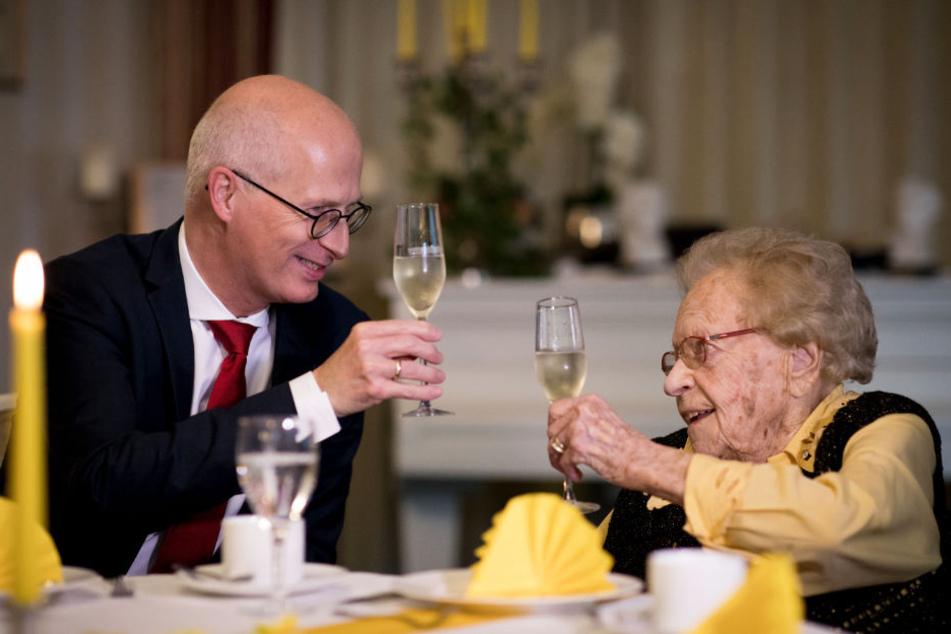 Tschentscher zeigt sich auch bürgernah. Zusammen mit Hamburgs ältester Einwohnerin, Lydia Smuda, stößt er auf ihren 112. Geburtstag an.