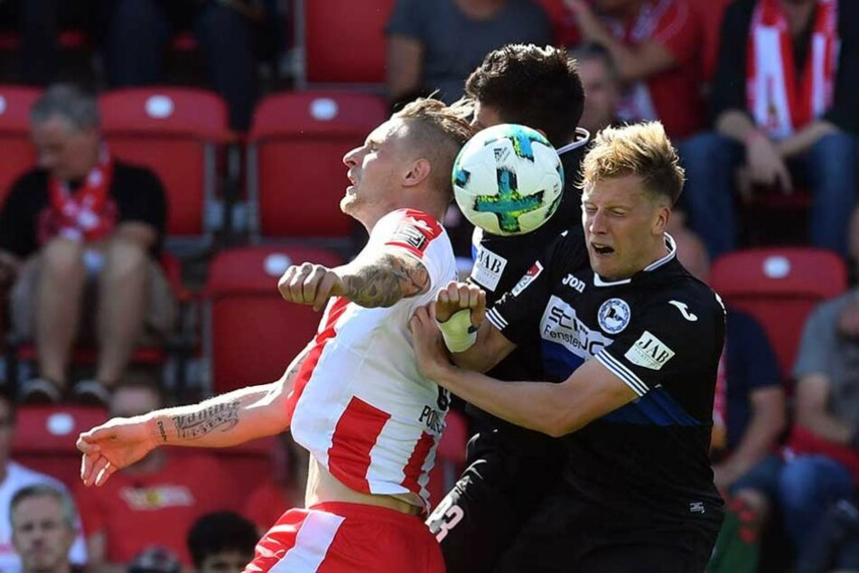Sebastian Polter (l) vom 1.FC Union Berlin gegen Florian Dick (M) und Christoph Schösswendter von Arminia Bielefeld.