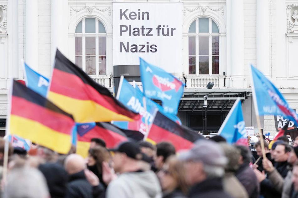 """Teilnehmer einer AfD-Demo schwenken am in Hamburg Fahnen vor dem Deutschen Schauspielhaus von dem ein Plakat mit der Aufschrift """"Kein Platz für Nazis"""" herunter hängt. (Symbolbild)"""