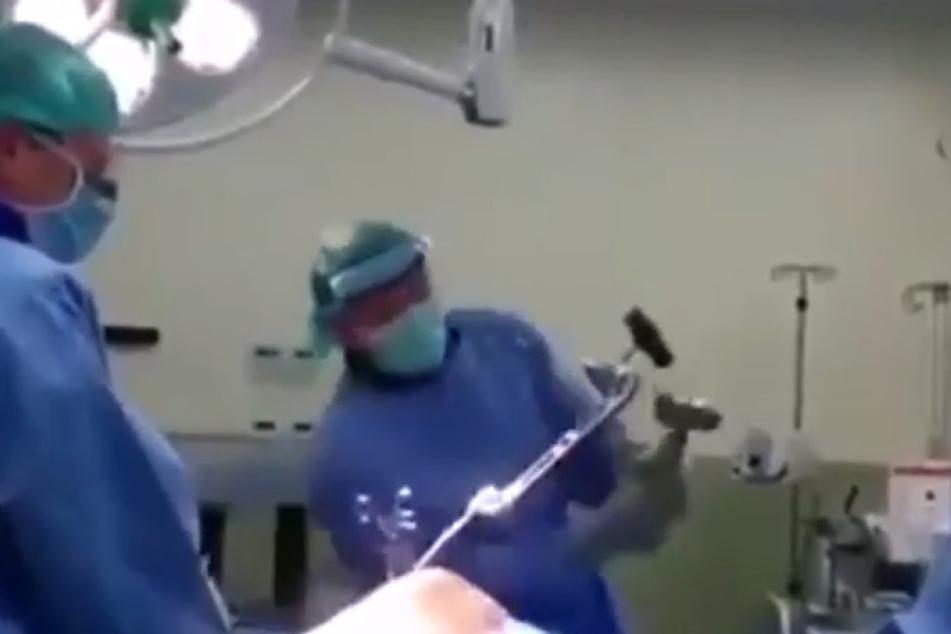 Diese Bilder lassen einen erschaudern: ein Arzt kloppt bei einer Operation mit einem Hammer auf eine Stange ein, die noch im Bein des Patienten befestigt ist.