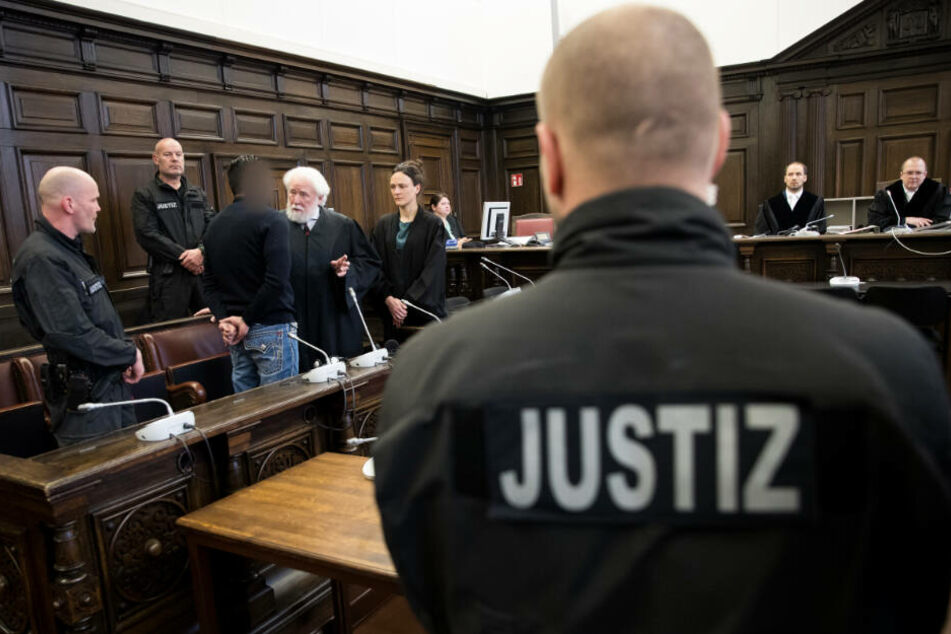 Der Angeklagte unterhält sich mit seinen Verteidigern im Gerichtssaal. (Archivbild)