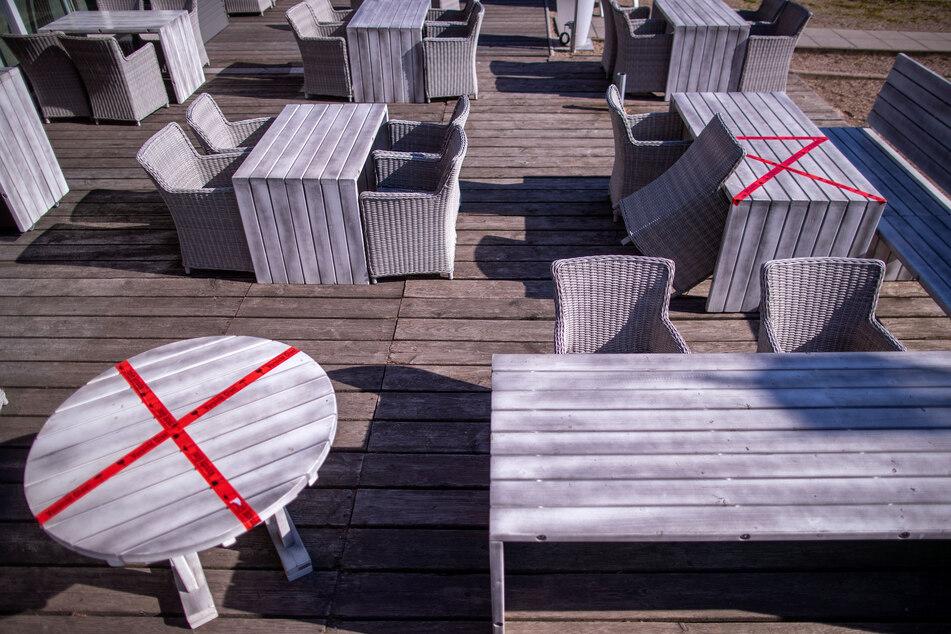 In einem Freiluftrestaurant am Schweriner See sind einzelne Plätze für die Einhaltung der geforderten Abstände mit rotem Markierungsband abgesperrt.