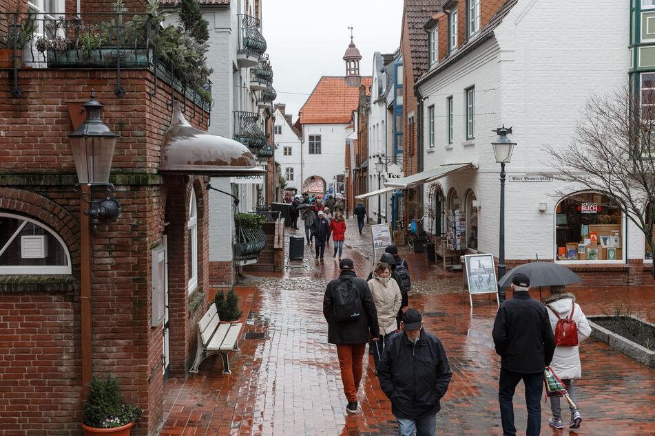 Passanten gehen gehen durch den Schlossgang in Husums Altstadt.